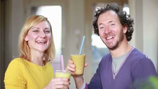 Close-up of happy couple toasting and drinking fruit smoothie, in slow motion
