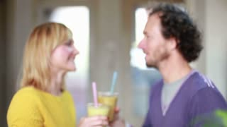 Close-up of happy couple toasting and drinking fruit smoothie