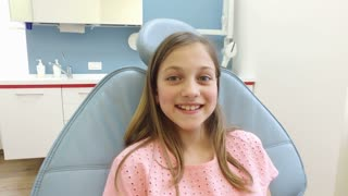 Close up of little girl at dentist, looking at camera and smiling