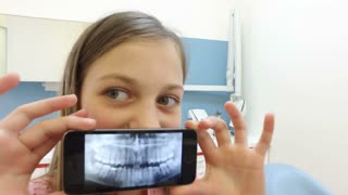 Close up of little girl holding smartphone with photo of dental x-ray