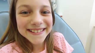 Close up of little girl sitting in the dental chair and smiling