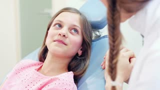 Close up of little girl sitting in the dental chair talking with dentist