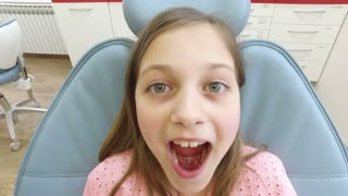 Close up of little girl sitting in the dental chair with open mouth