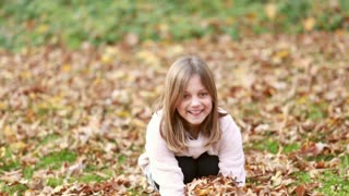 Close up of lovely young girl throwing leaves in park in autumn