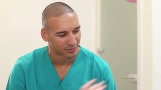 Close up of male dental surgeon talking with patient