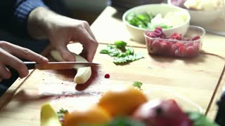 Close-up of man hand cutting banana for fruit shake on wooden board, graded