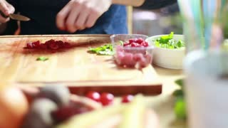 Close-up of man hands cutting raspberries for smoothie on wooden board
