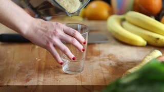 Close-up of pouring fruit smoothie into drinking glass
