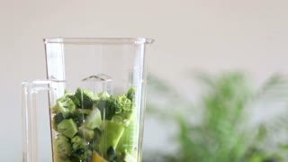 Close-up of pouring water in blender with pieces of fruit and vegetables, in slow motion