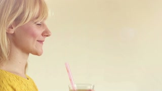 Close-up of profile face of a young woman drinking smoothie, graded