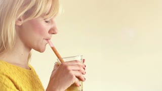 Close-up of profile face of a young woman drinking smoothie, in slow motion, graded