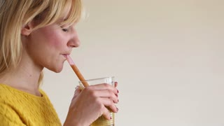 Close-up of profile face of a young woman drinking smoothie, in slow motion