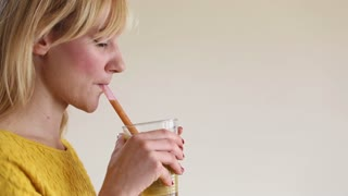 Close-up of profile face of a young woman drinking smoothie