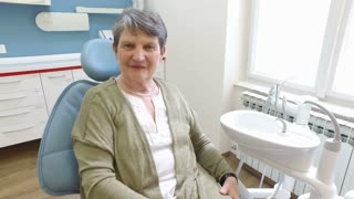 Close up of smiling elderly female patient at dentist