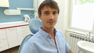 Close up of smiling man with healthy white teeth at dentist