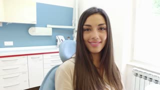 Close up of smiling woman looking at camera while sitting in the dental chair