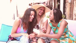 Close up of three beautiful and attractive young women having a lot of fun while taking selfies on terrace cafe on a summer day,  graded warmer.