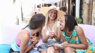 Close up of three beautiful and attractive young women having a lot of fun while taking selfies on terrace cafe on a summer day.