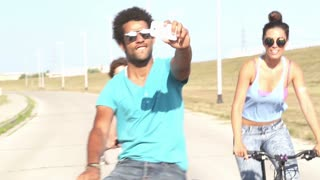 Close up of three young adults cycling outdoors and having fun taking selfies, graded