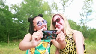 Close up of two beautiful young women having fun while taking selfies of themselves using a mobile phone.