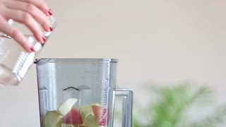 Close-up of woman hand pouring water in blender with pieces of fruit, slow motion