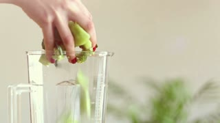 Close-up of woman hand putting food in blender, graded