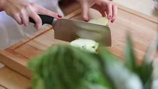 Close-up of woman hands cutting apple on pieces on wooden board, fast forward