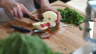 Close-up of woman hands cutting apple on slices, graded