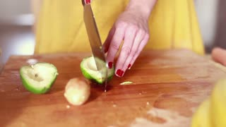 Close-up of woman hands cutting avocado on slices, graded