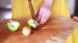 Close-up of woman hands cutting avocado on slices