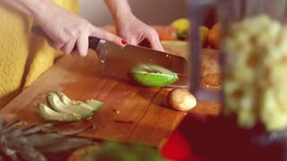 Close-up of woman hands cutting avocado on wooden board before blending, in slow motion, graded