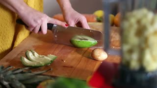 Close-up of woman hands cutting avocado on wooden board before blending