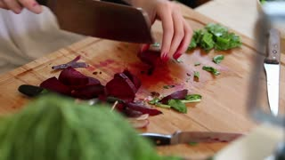 Close-up of woman hands cutting beetroot on wooden board