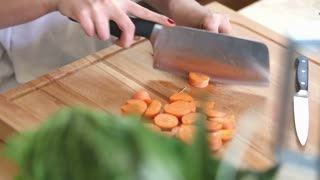 Close-up of woman hands cutting carrot on wooden board, graded