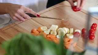 Close-up of woman hands cutting cherry tomatoes on wooden board