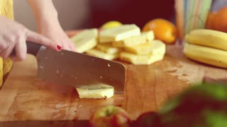 Close-up of woman hands cutting pineapple into pieces on wooden board, graded
