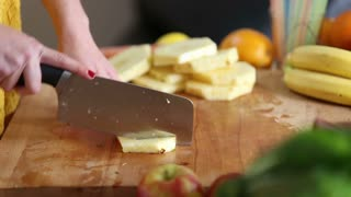 Close-up of woman hands cutting pineapple into pieces on wooden board