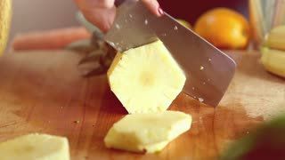 Close-up of woman hands cutting pineapple into slices on wooden board, graded