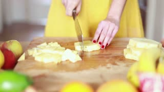 Close-up of woman hands cutting pineapple on small pieces for fruit shake, graded