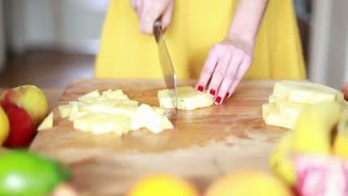 Close-up of woman hands cutting pineapple on small pieces for fruit shake