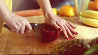 Close-up of woman hands cutting pomegranate on wooden board, in slow motion, graded