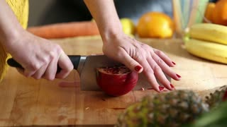 Close-up of woman hands cutting pomegranate on wooden board, in slow motion