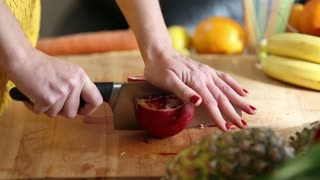 Close-up of woman hands cutting pomegranate on wooden board