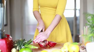 Close-up of woman hands cutting pomegranate
