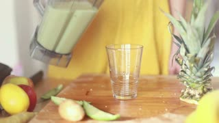 Close-up of woman hands pouring fruit smoothie in drinking glass, in slow motion, graded