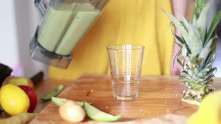 Close-up of woman hands pouring fruit smoothie in drinking glass, in slow motion