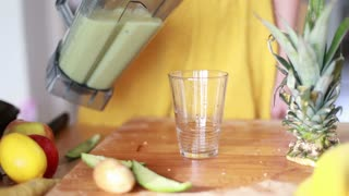Close-up of woman hands pouring fruit smoothie in drinking glass