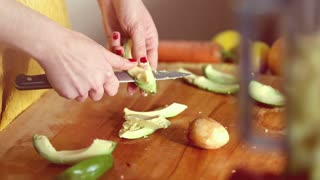 Close-up of woman hands slicing avocado on wooden board, graded