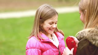 Close up of young blonde mom putting cap on daughter's head and kissing her in forehead in park, graded