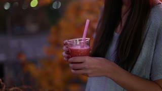 Close-up of young brunette woman drinking fruit smoothie, in slow motion